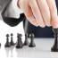 Business man moving chess figure with team behind - strategy or leadership concept